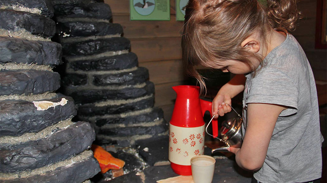A girl pouring drink into her cup in Fell Lapland visitor centre.