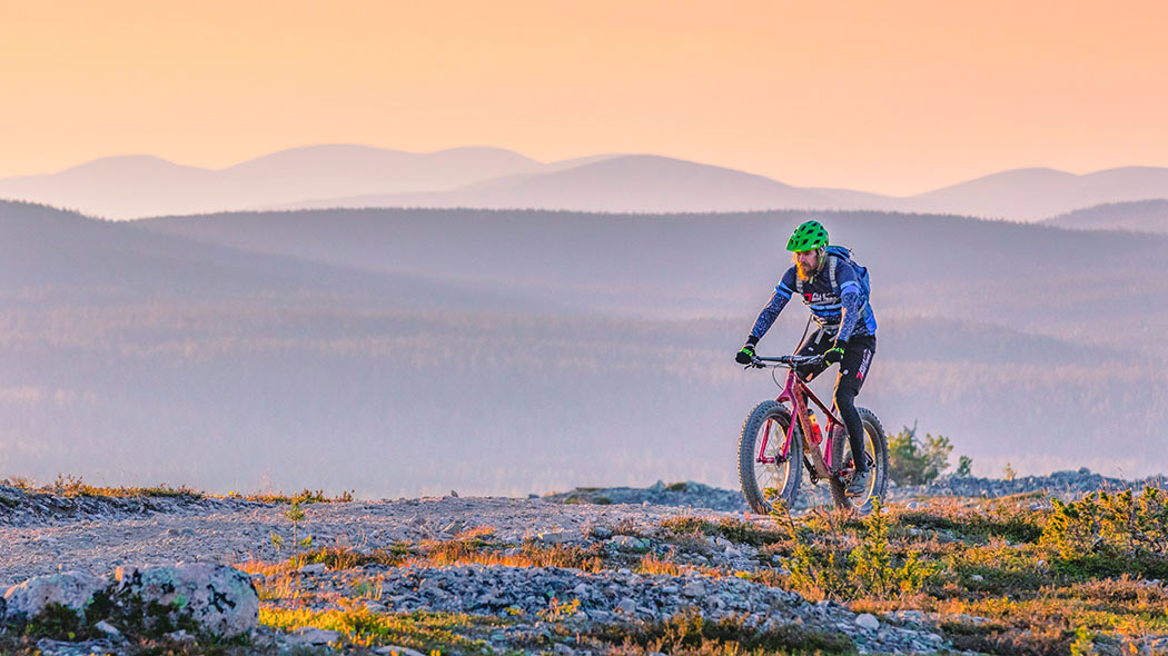 A mountain biker on a gravel path on top of a fell. Fells can be seen in the background and the sun is low in the sky. Vegetation in autumn colours can be seen in the foreground.