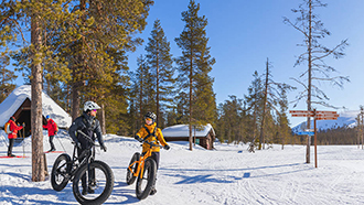 Two people standing in the snow, leaning against black fat bikes in the foreground. There is a lapp-hut and a woodshed in the background and pine forest and a blue sky can be seen in the wintry landscape.