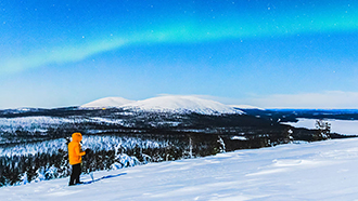 A snowshoer in the open fell landscape. The terrain is covered in snow and white fells and a dark forest can be seen in the background. Northern lights are lighting up the sky.