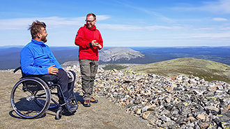Two men on top of a fell on a sunny day. One man is sitting in a wheelchair and the other man is standing next to him. A row of fells can be seen in the background.