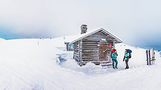 A small log cabin with a chimney made of stone in an open, snow-covered fell landscape. Two hikers with backpacks are standing in front of the cabin. There are two pairs of skis standing in the snow and the sky is overcast.