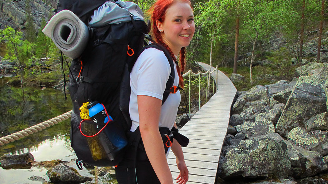 A person with a backpack is standing on a wooden bridge.