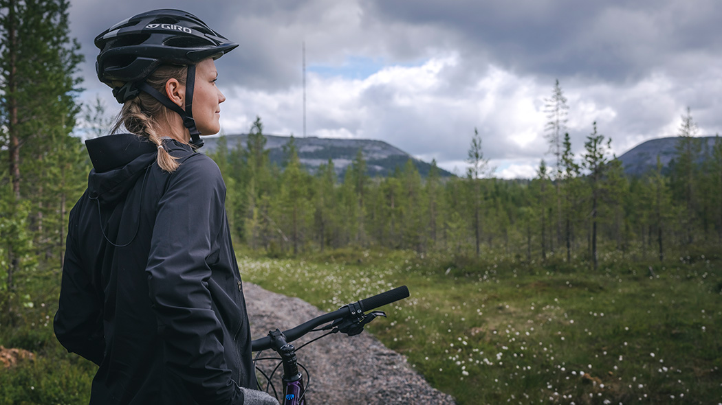 A cyclist with a helmet has stopped to admire the views on a mountain bike trail. There's fells and a cloudy sky in the background.