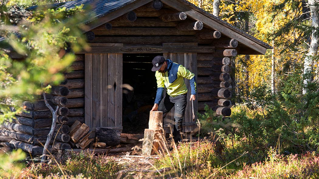 A person chopping wood in the forest in front of a lean-to shelter.