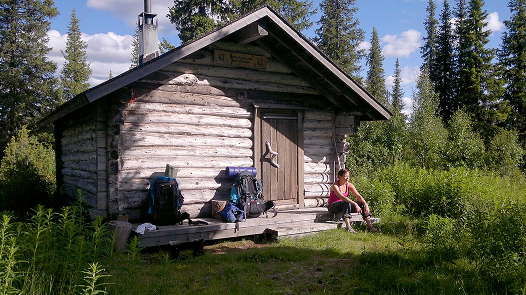 A person sitting in the sunshine in front of a logwood hut with two backpacks next to them.