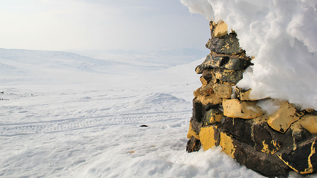 Halti border cairn covered in snow. A snowy landscape with snowmobile tracks can be seen in the surroundings.