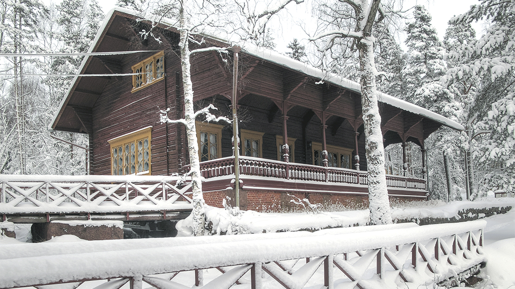 In the winter landscape a dark wooden building with a large porch. Some trees in front of the building and a snowy forest behind.