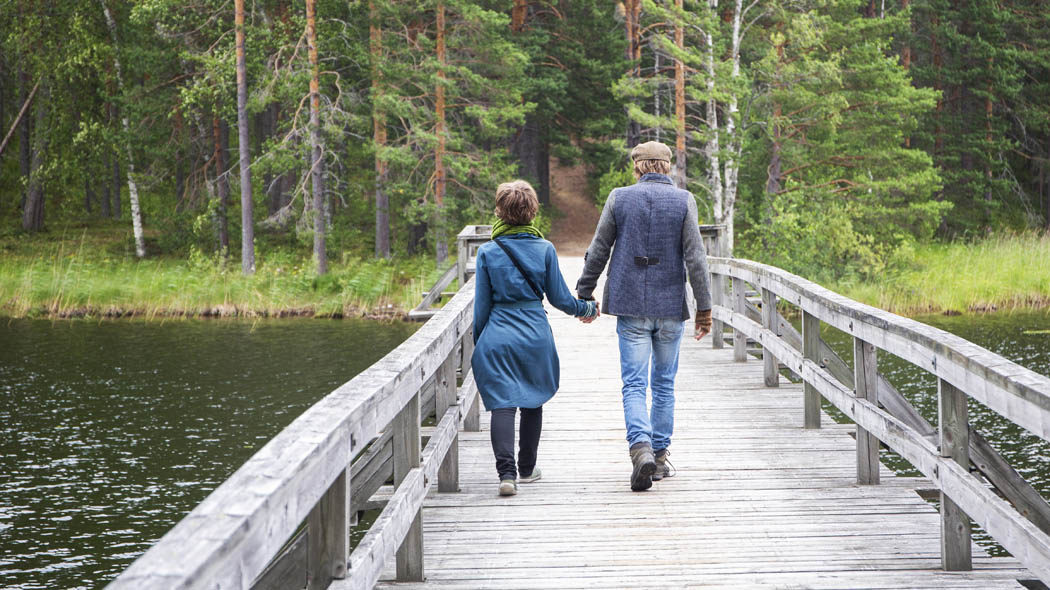 Two persons walking hand in hand away from the camera across an old grey wooden bridge. The path continues through a pine forest after the bridge.