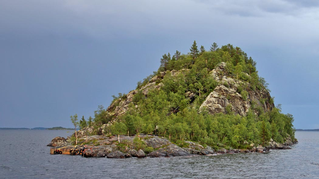 A tall rocky island rising from the water. There are tall cliffs on one side and lower flat rock on the other side. Small trees are growing on the island. The sky is dark and cloudy.