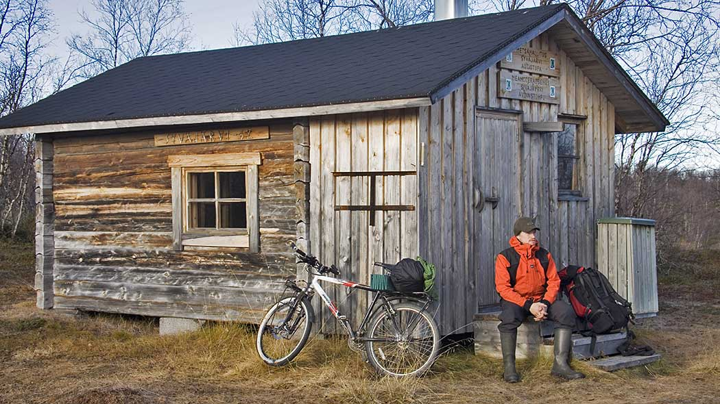 A hiker taking a break at Syväjärvi open wilderness hut.