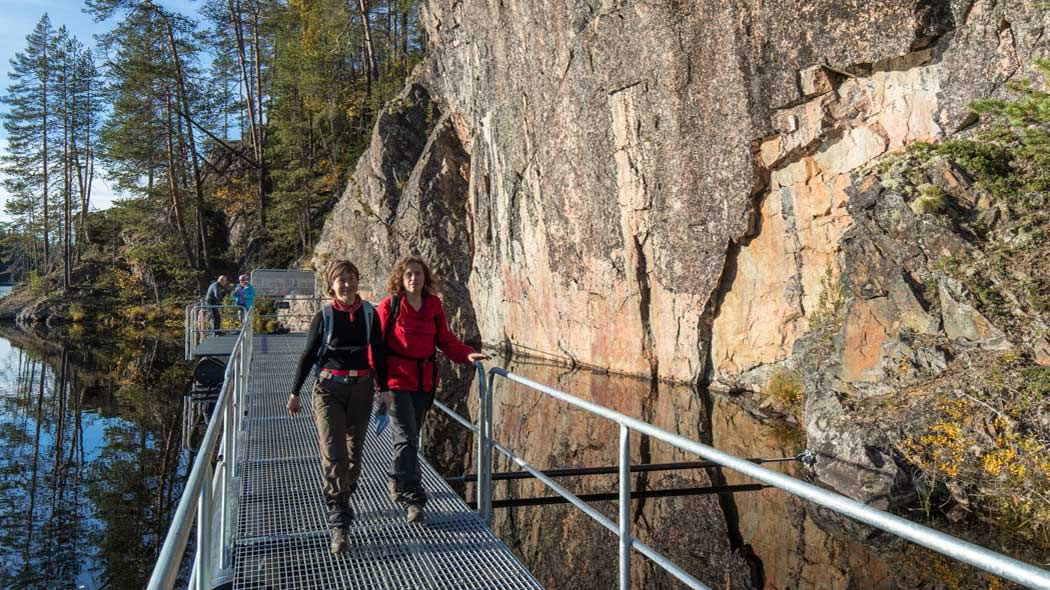 Two persons walking on a footbridge made of a thick metal mesh. The footbridge follows a cliff along the lakeshore. Two persons can be seen in the background.