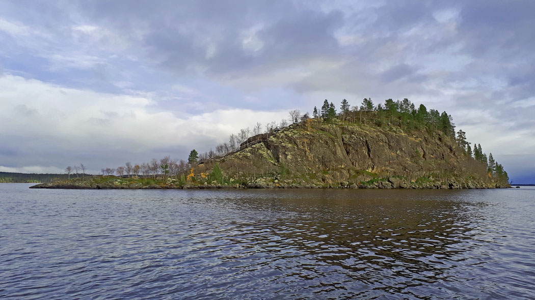An island with tall cliffs rising from the water. Leafless trees are growing on the island. The sky is cloudy and dull.