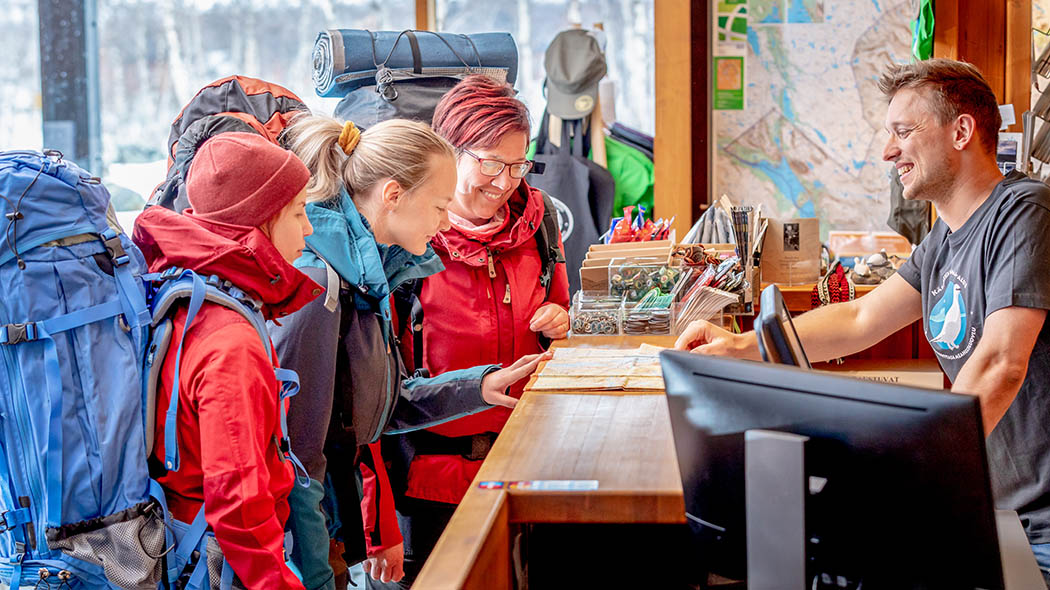 Three hikers with large backpacks have arrived at the service desk of Kilpisjärvi visitor centre. Kilpisjärvi Visitor Centre provides information for tourists, hikers and fishers. Photo: Rami Valonen.