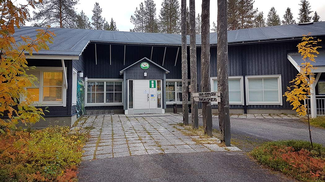 Entrance to Savukoski Nature Centre Korvatunturi, which is located on ground-level. On front of the building is a sign with text Urho Kekkosen Kansallispuisto and autumn foliage rowans and twigs.