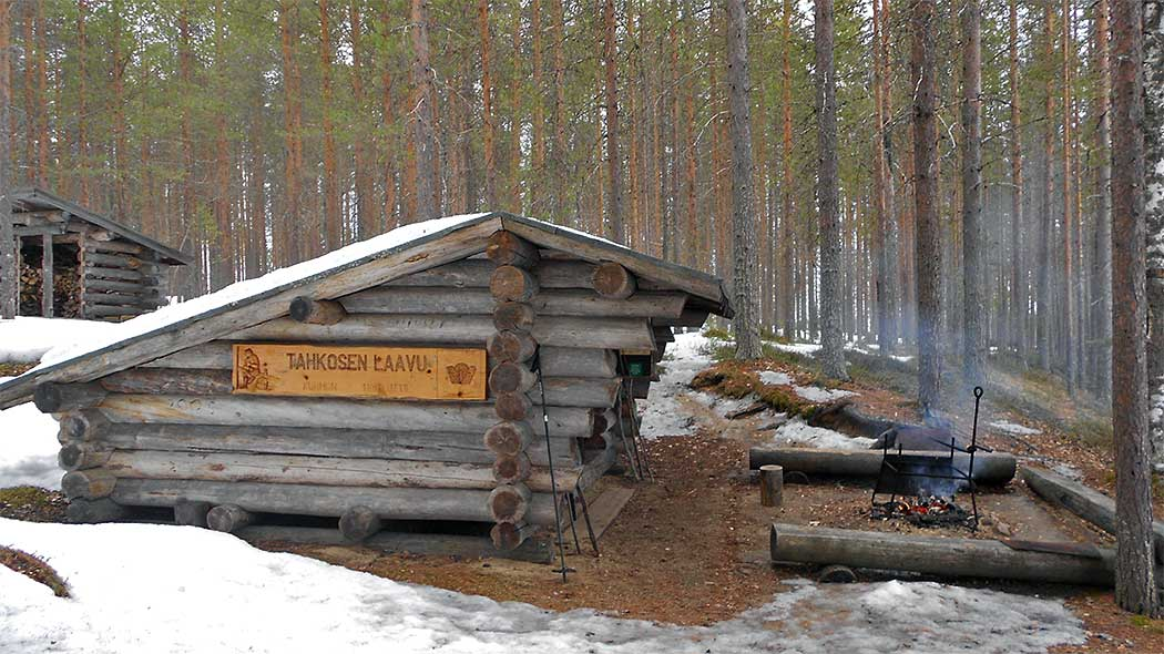Lean-to-shelter and a campfire ring. On the side of the shelter is a wooden plate with a text: Tahkosen Laavu.