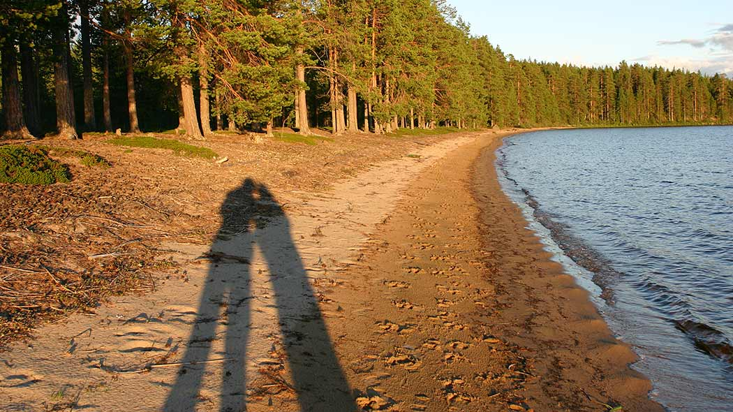 Shadows of two hikers on a sandy beach.