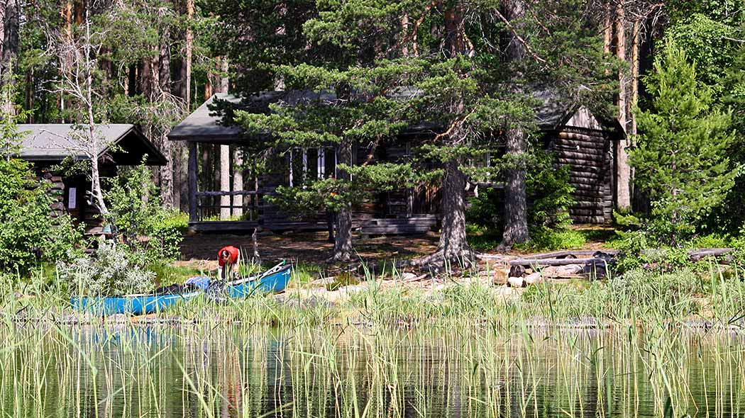 Open wilderness hut surrounded by pine forest. Hiker and a boat can be seen on the reedy shore.