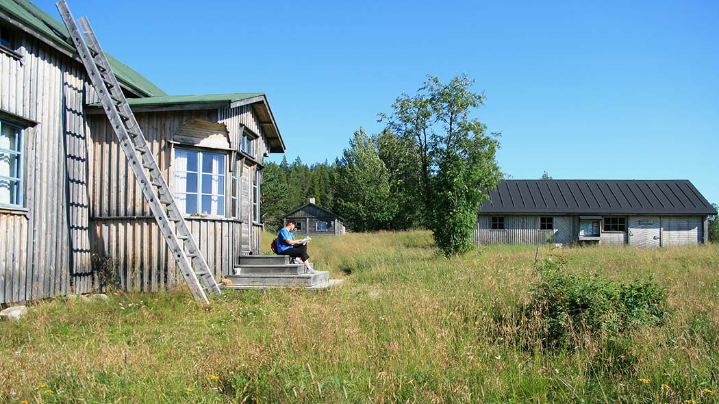 A person sitting on the stairs of a wooden building. A meadow and a sauna can be seen in the background.