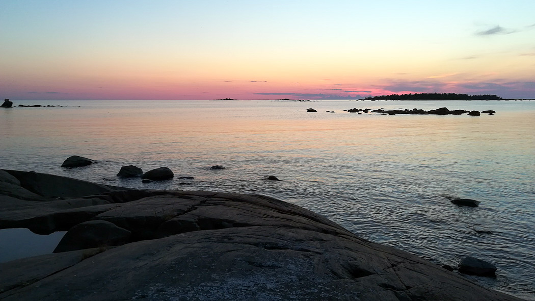 A summer evening on the rocky island. The sun is setting on the horizon, where islets can be seen. The sky is coloured red and purple.