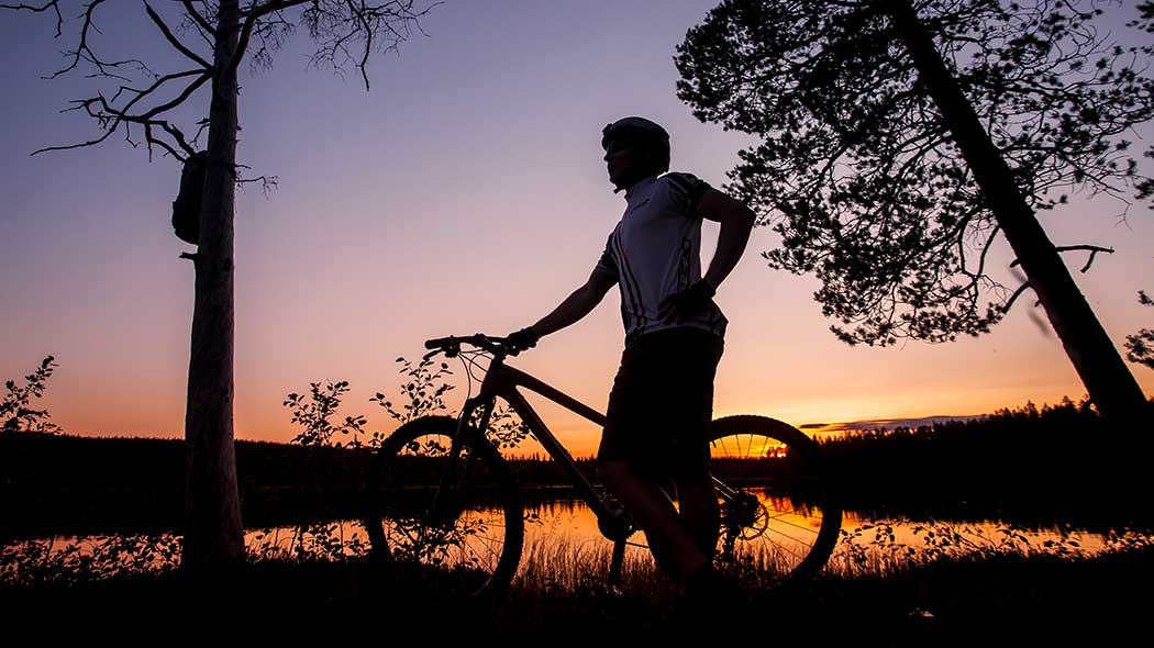 A person with a bike next to a lake with sun setting on the background in the evening.