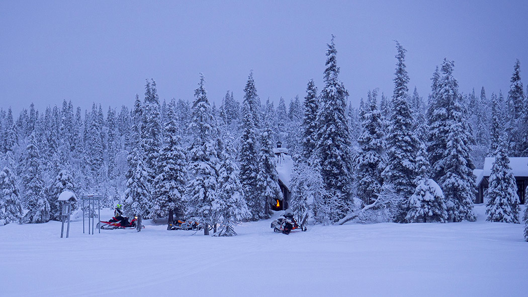 Winter landscape, snowy spruces. In the midst of the trees you can see snowmobiles and a kota-hut with an open door with a fire visible.