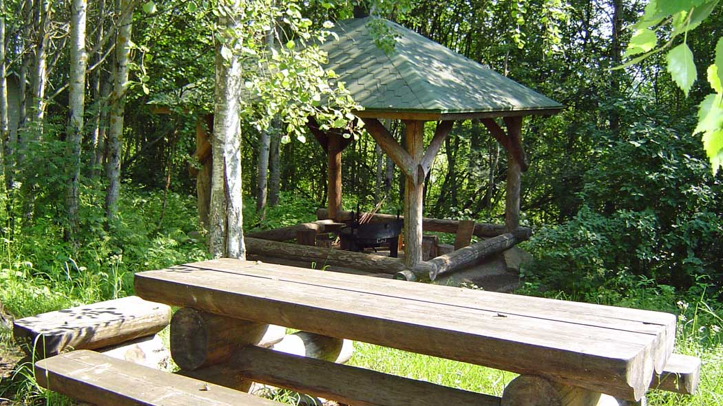A table and benches made of big logs on the yard, there is also a roof-covered firepit.