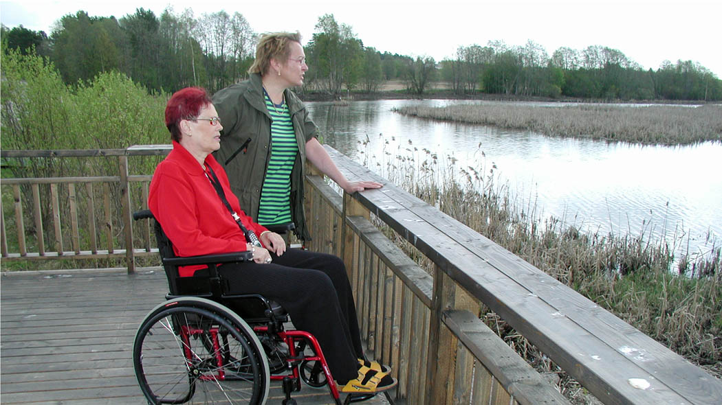 Two persons looking out over the wetlands from a low and open viewing platform. One person sits in a wheelchair.