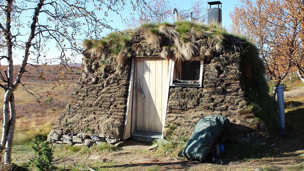 Old turf hut, surrounded by mountain birches and fell vegetation. There's a backpack by the door of the shelter.