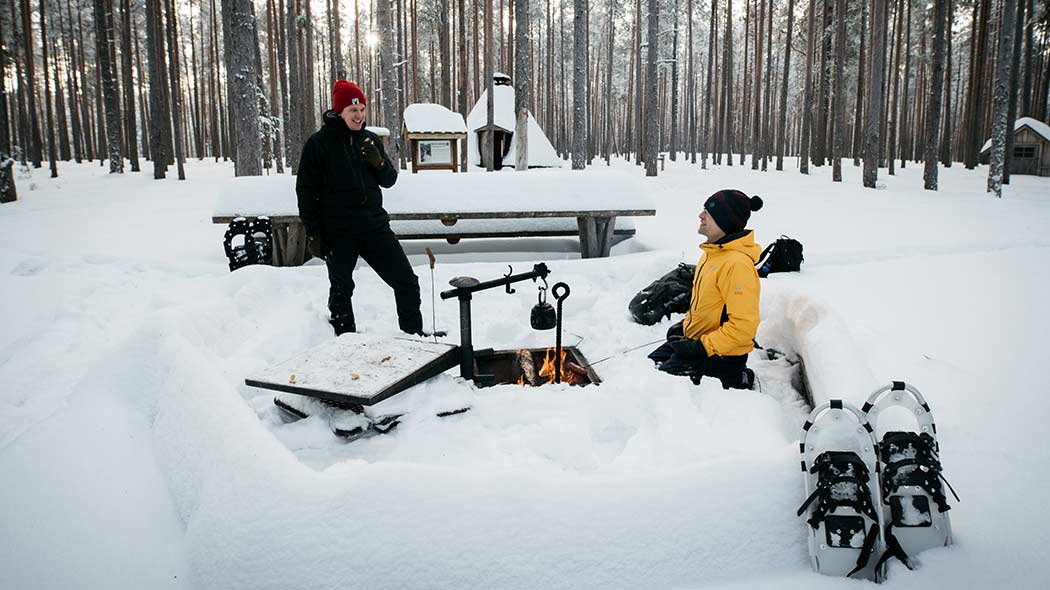 Two snowshoers taking a break at a campfire site.