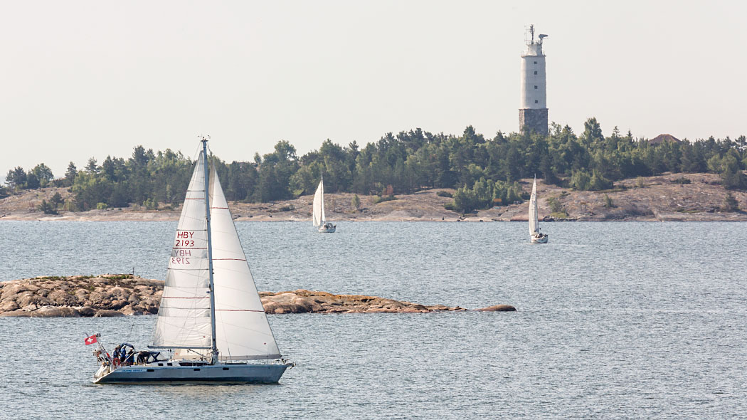A sailboat with two sails sailing in a light breeze. Two more sailboats can be seen in the background and behind them a rocky shore where there is a lighthouse and pine trees.