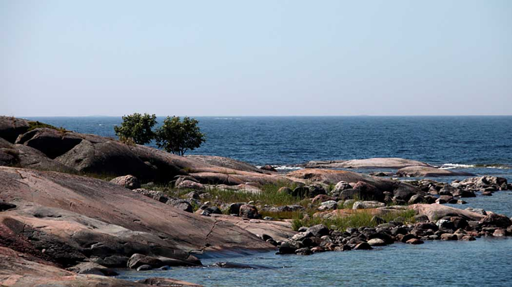A Stony peninsula in a summery landscape. The sea is rough.