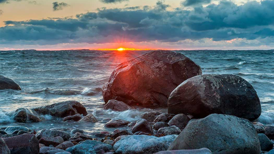 A stony shore in the sunset. The sky is partly cloudy and waves can be seen in the background. The sun casting its last rays before setting on the horizon.