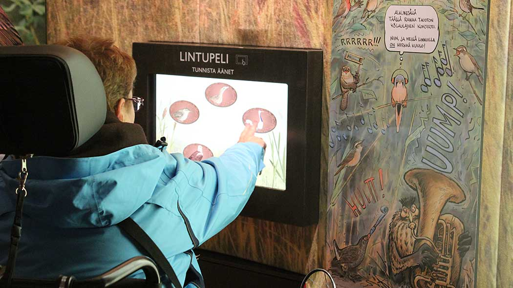 A hiker in a wheelchair is using a touch screen to play a bird-themed game on the wall in a visitor centre.