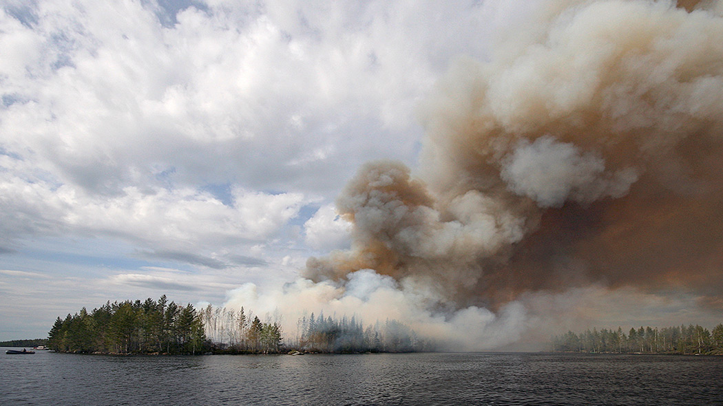 In the foreground there is a lake, with a central island. The forest on the island is burning in a controlled manner. Thick, gray smoke is rising up from the burning forest.