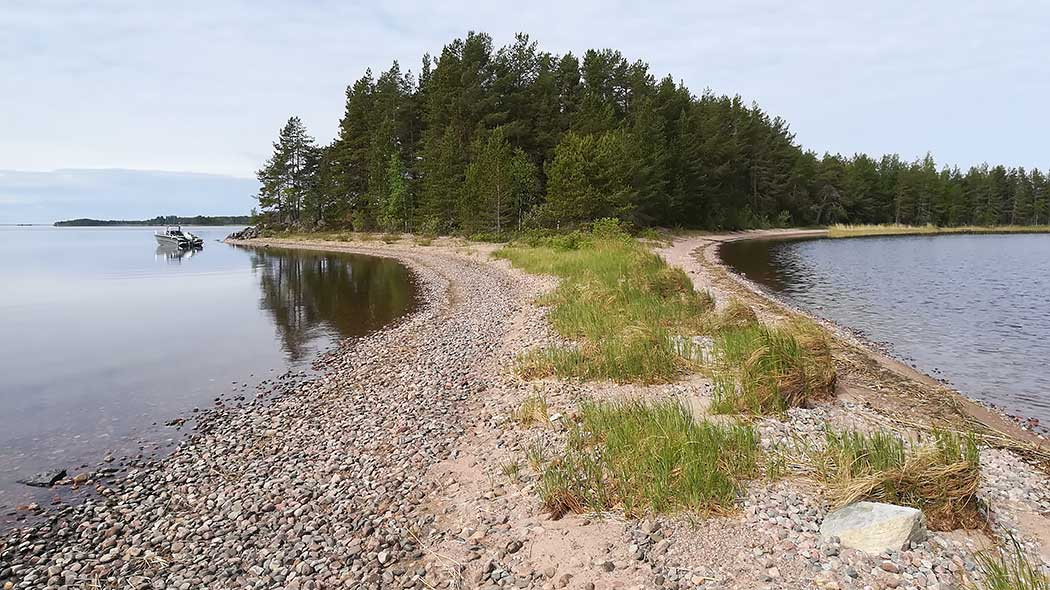 A narrow and stony isthmus between two water areas. To the left is a motorboat tied to the forest-covered shore.
