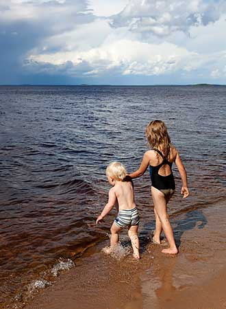 Two children wading through the shallow water at a beach.
