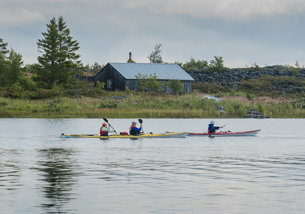 Three persons paddling in two canoes on a calm day. A fisherman's hut on the shore in the background, a tall spruce tree and a stony esker.