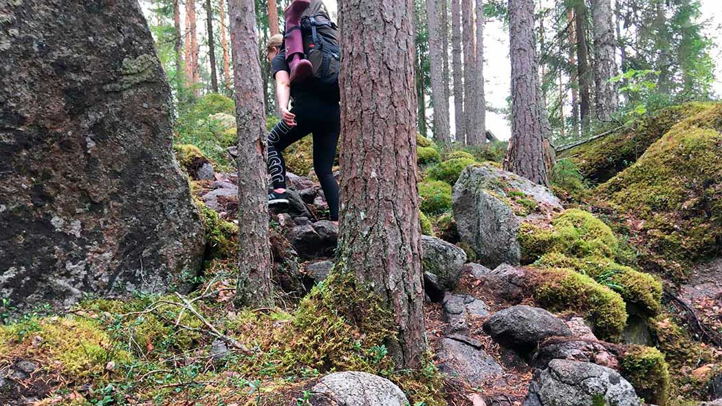 A hiker wearing a backpack is climbing up a very rocky slope. Some of the rocks are covered with moss.
