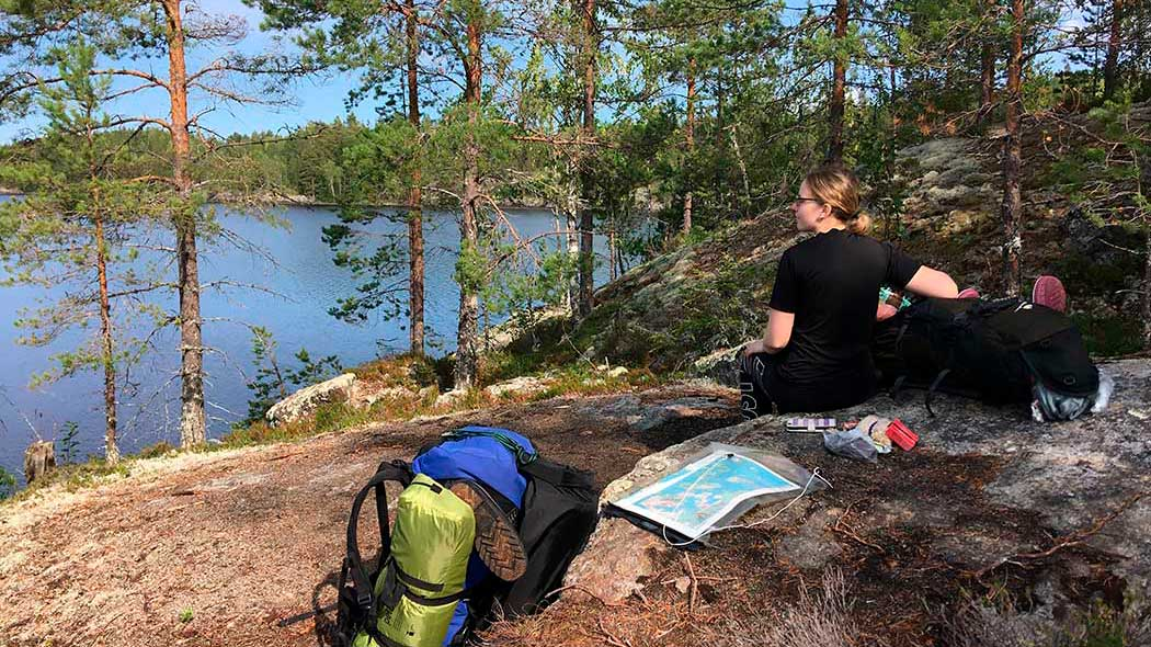 A hiker sits atop a cliff, overlooking a lake. A backpack, map and other camping equipment are laid out on the cliff.