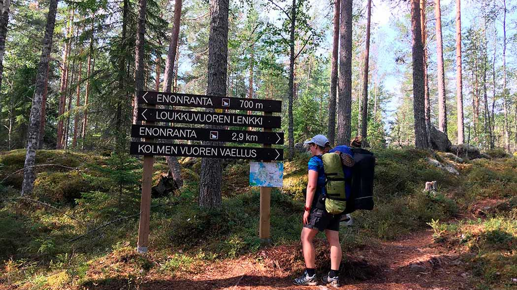 A hiker stands in front of some signs, and examines a map. The signs provide directions to various destionations.