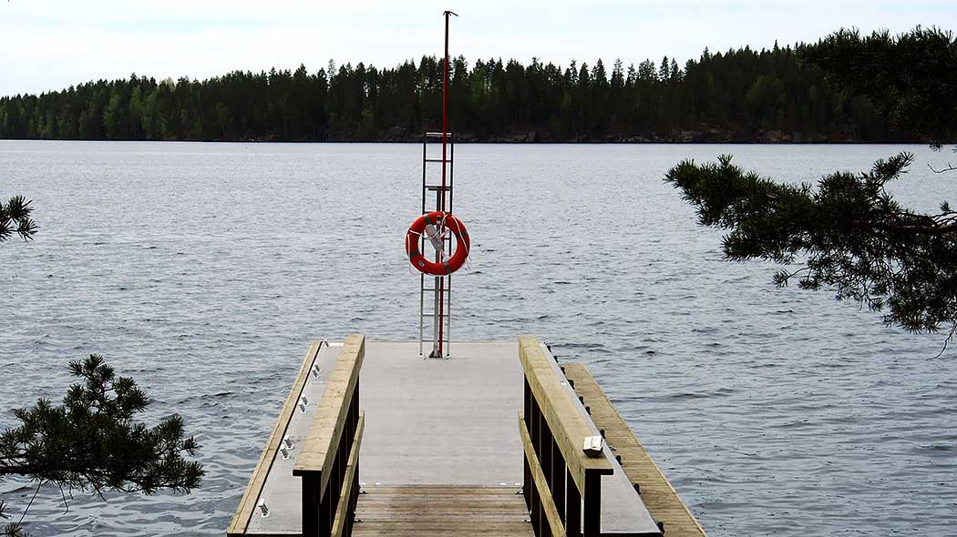View form the shore out towards a lake, with a jetty extending straight into the water. The jetty has a lifebuoy. On the opposite beach is forest.