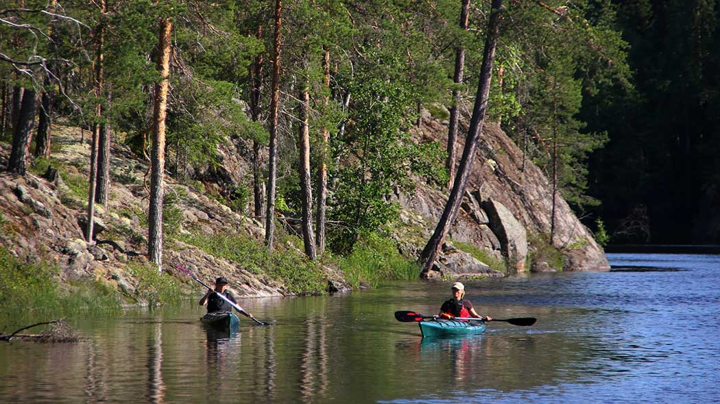Two kayak paddlers on a sunny lake near a steep, rocky slope.