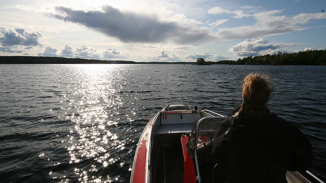 A woman is driving a motorboat towards the sun in an open lake landscape.