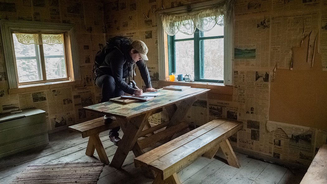 A day-trip hut photographed from the inside. One person sitting at the wooden table. The walls are lined with old newspapers.