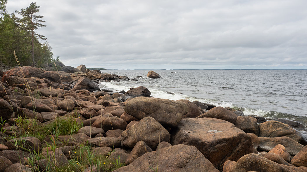 A sea shore with big boulders.