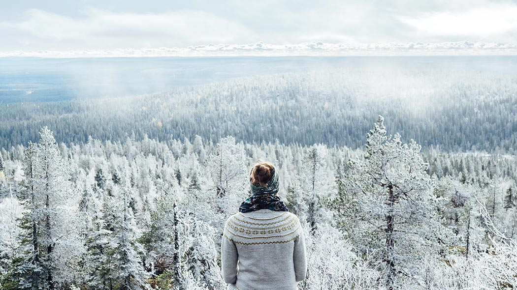 A hiker admiring wintry forest view from Iso-Syöte fell.