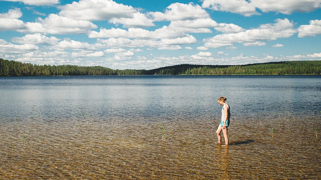A hiker wading in shallow water at Lake Rääpysjärvi.