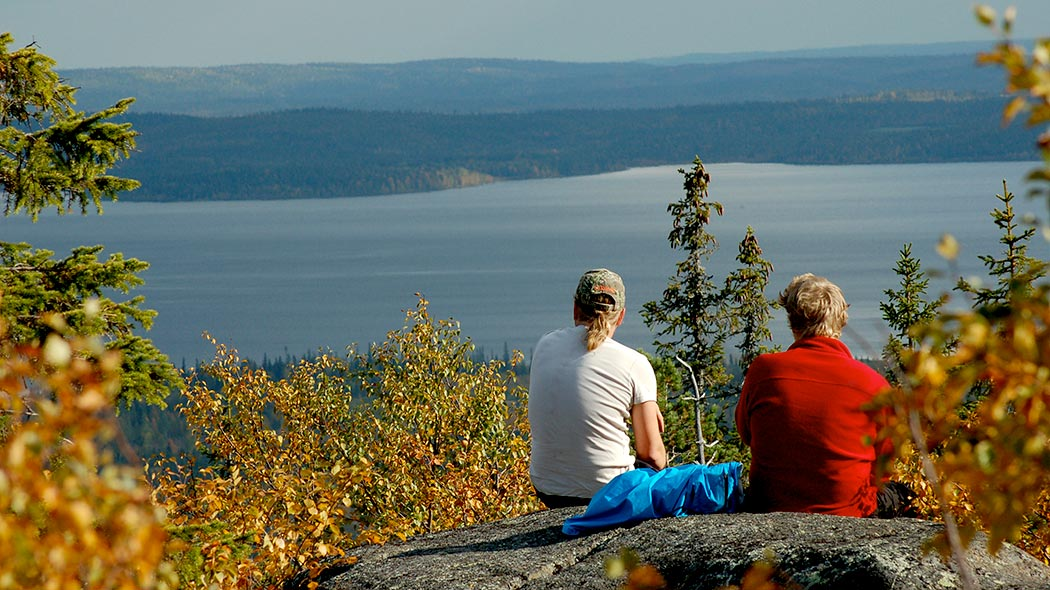 Two hikers admiring a view of lake and forests from the top of Pyhitys hill.