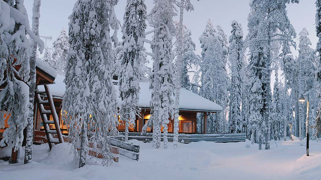 Syöte Visitor Centre during winter, surrounded by snow-covered trees.